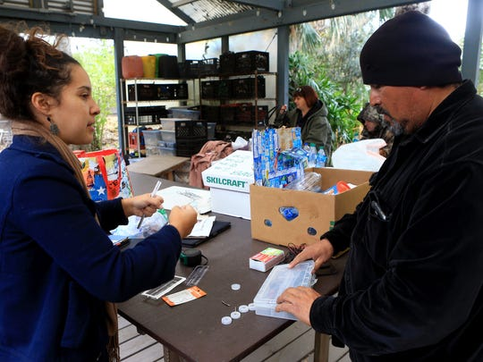 Melissa Zamora (left) talks about items she needs with John Meza as they work on a bottle sculpture after the Corpus Christi's recent water crisis on Saturday, Jan. 28, 2017, in Corpus Christi.