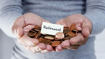 Man with his hands full of pennies and a small sign in the middle with the word Retirement