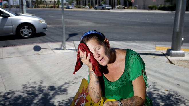 Amanda Ouellet wipes her face with a cold wet towel to cool off while working outside holding an advertising sign in Las Vegas in July 2014.