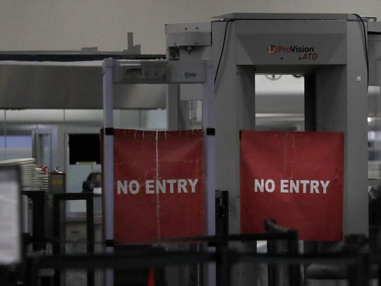 Travelers are permitted from entering a closed down terminal at the Miami International Airport on Saturday, Jan. 12, 2019, in Miami. The partial government shutdown is starting to strain the national aviation system, with unpaid security screeners staying home, air-traffic controllers suing the government and safety inspectors off the job. (AP Photo/Brynn Anderson)