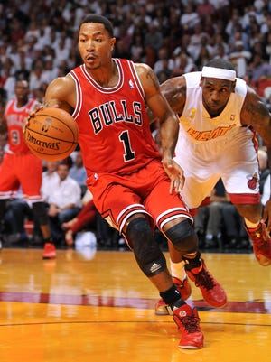 Bulls point guard Derrick Rose drives past Heat forward LeBron James during Tuesday's season-opening loss.