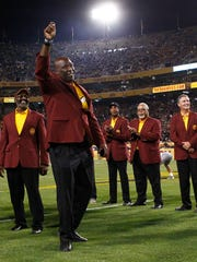 Former Arizona State player Jim Jeffcoat waves during