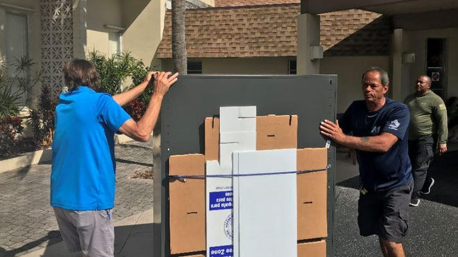 Ballots are wheeled into the Sunlight Community Church in Lake Worth Beach nearly four hours after voting began Tuesday morning.