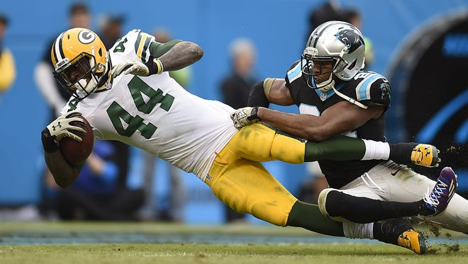 Green Bay Packers running back James Starks (44) dives into the end zone for a touchdown while being tackled by Carolina Panthers cornerback Josh Norman (24) during Sunday's game at Bank of America Stadium in Charlotte, NC.