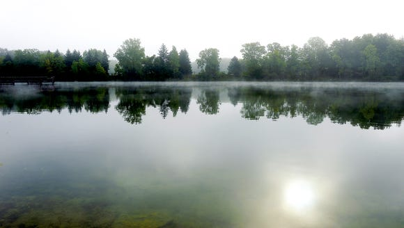 Steam rises from the pond at Crego Park during a foggy
