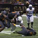 Southern running back Lenard Tillery loses the ball after being tackled by a group of Grambling State defenders Saturday in New Orleans.