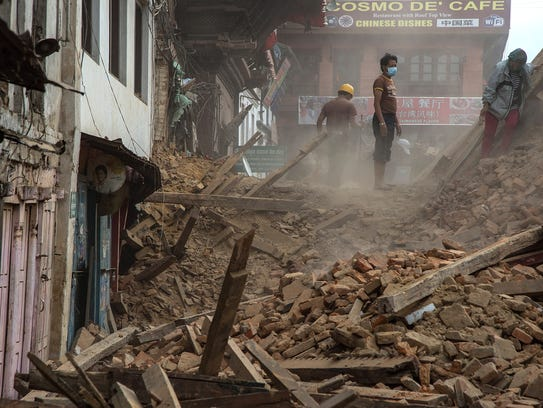 Volunteers and quake emergency team members clear debris