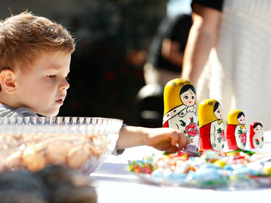 Lucas Illyuk, 3, reaches for some candy at one of many