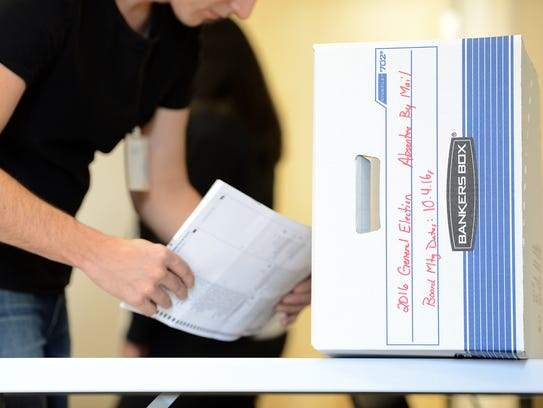 Kent Mettle files scanned ballots into a box as he