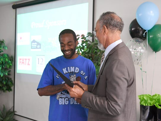 Damion Smith receives a certificate from Asheville