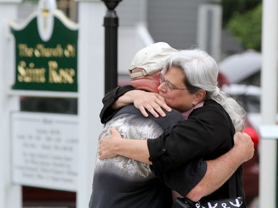 People embrace outside the Church of St. Rose in Belmar
