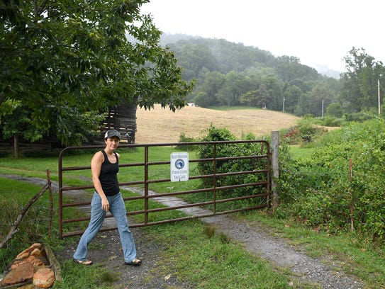 Laura Boggess closes a gate that leads to the trailhead