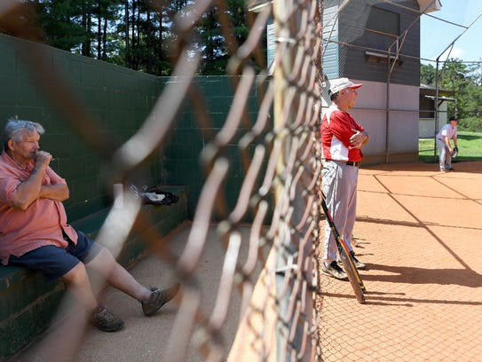 Mickey Trinite, left, watches the action from the dugout