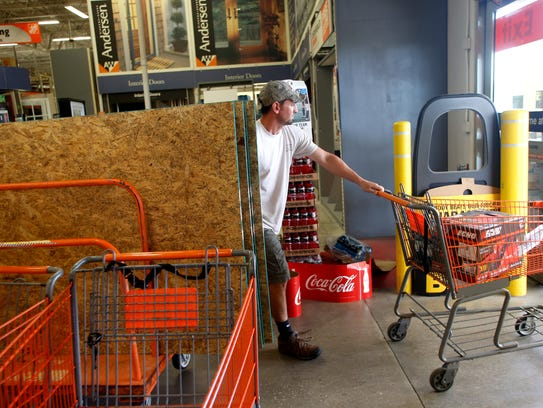 Shoppers gather supplies at a Home Depot store as residents