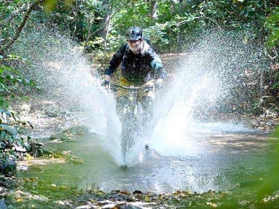 John Cromwell splashes through a creek as he demonstrates