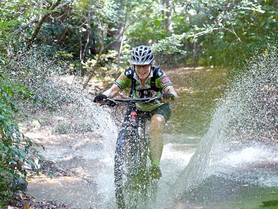Tracey Armstrong splashes through a creek as she demonstrates