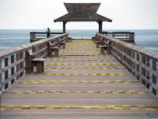 Caution tape lines the second half of the Naples Pier, which is missing its end railing, on Sept. 21, 2017.