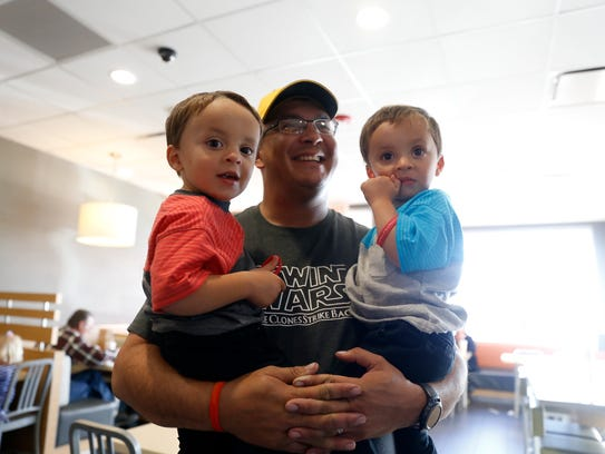 Bjorn Baal holds his twin sons, Thiago Baal, left, and Zander Baal, Wednesday at McDonald's in Farmington.