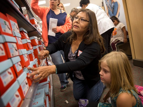 Volunteer Cheryl Martin helps Kira Spires search for boots Thursday during the Rio del Sol Kiwanis Club's Clothes for Kids event at Target in Farmington.