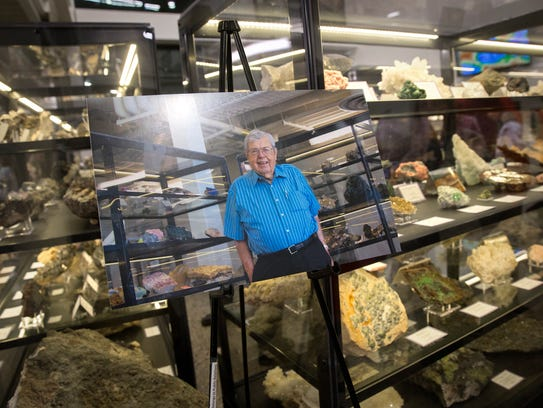 A portrait of the late Tom Dugan sits near a display of minerals and fossils on Wednesday at the Sherman Dugan Museum at San Juan College in Farmington.