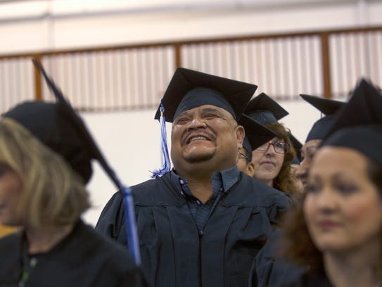 Nelson Bee reacts before the start of the Charter Institute's commencement ceremony Friday at the McGee Park Convention Center.