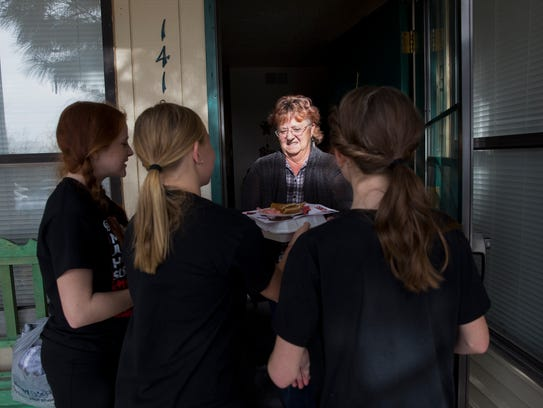 Caregiver Lynn Markle receives a meal from Hermosa Middle School students Alyssa Taft, left, Emily Black and Bria Cohen Thursday at the Apple Ridge Apartments in Farmington.