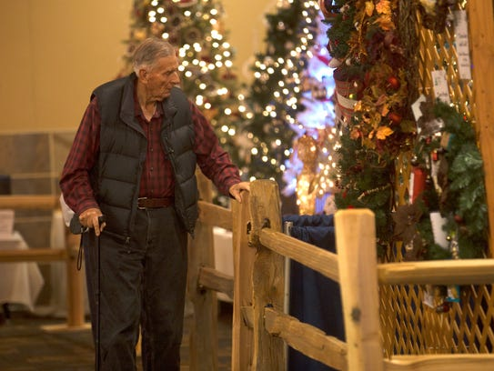 Lay Briggs checks out one of the displays Tuesday at the Festival of Trees at the Farmington Civic Center.