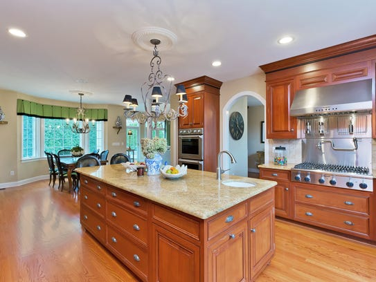 The kitchen features a huge granite stone center island and stainless steel appliances.