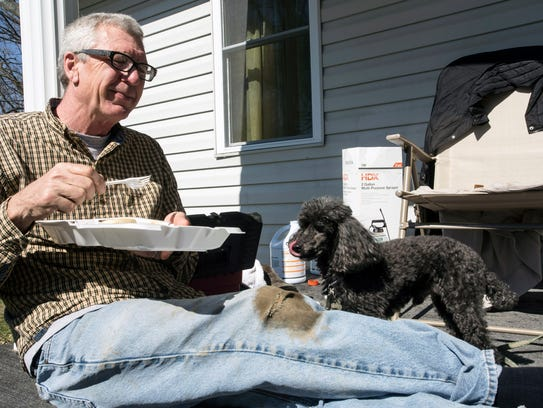 Joe Currell and his poodle Nick take a food break during