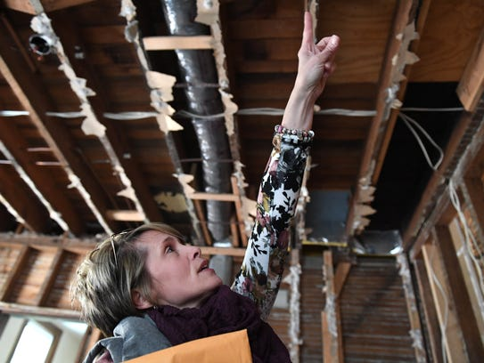 Tina Davenport points out the fire damage in her kitchen