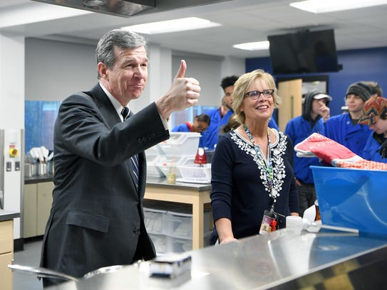 Governor Roy Cooper gives students in Lynn Isgrig's Foods II class a thumbs up after tasting pancakes they made as he takes a tour of Roberson High School in April. Cooper announced that his new budget will include increased funds for school safety from several angles.