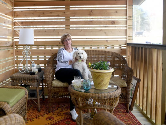 Pam Mcmasters sits with her dog, Willie, on the screened-in