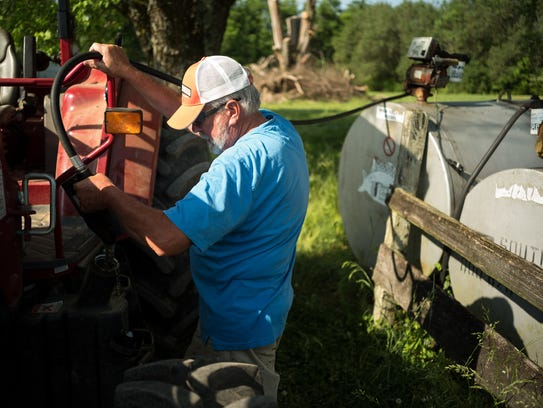 Bob Strasser refuels one of the tractors at his farm,