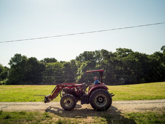 Bob Strasser drives a tractor at his farm, Tuesday,
