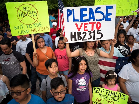 Demonstrators hold signs during a protest against HB 2315, a bill that will ban sanctuary cities in Tennessee, at Legislative Plaza in Nashville, Tenn., Wednesday, May 16, 2018.