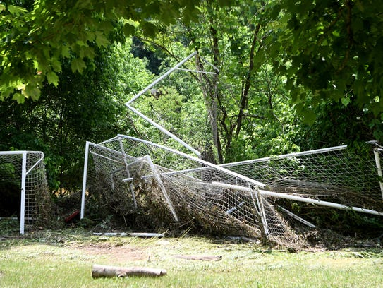 Soccer goals are piled together with debris near the