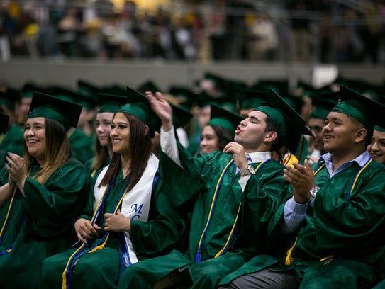 A graduate blows a kiss as a classmate receives their
