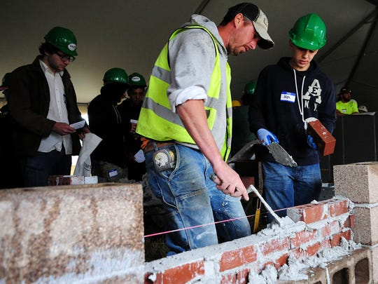 Beau Captain, of Kraft Masonry, helps Newberg High School student Alex Rosa build a wall during the 12th annual Construction Career Day at the Salem Airport, on Tuesday in Salem.