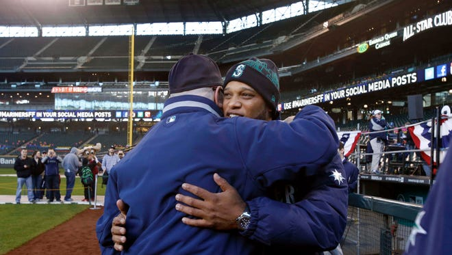 Robinson Cano, right, hugs general manager Jack Zduriencik during the Seattle Mariners' fan festival last month.