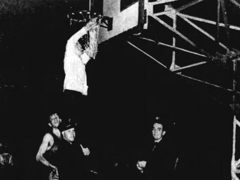 Frankfort student manager Leon Brower is photographed clipping the net at then-named Butler Fieldhouse as he was hoisted by an unidentified Indianapolis fireman.