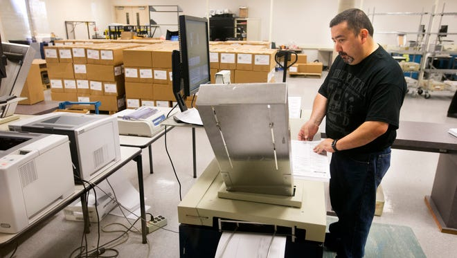 Maricopa County election official Gary Ramirez puts ballots through a machine that tabulates the results at the Maricopa County Elections building in Phoenix on Aug. 29, 2014.
