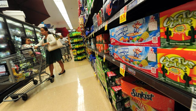 A woman shops an aisle with frozen foods, sodas and other sugary drinks at a supermarket in Monterey Park, Calif. on June 18, 2014.