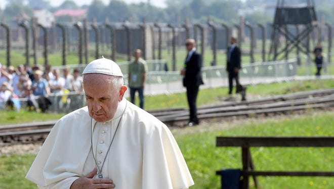 A solemn Pope Francis prays in front of the memorial in the former German Nazi concentration and extermination camp.