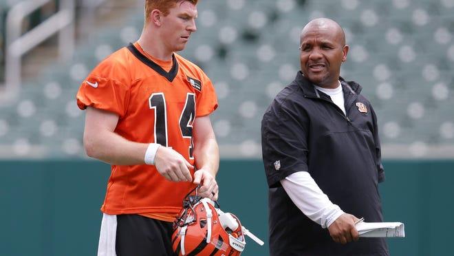 Cincinnati Bengals quaterback Andy Dalton (14) speaks with offensive coordinator Hue Jackson during an NFL football minicamp at Paul Brown Stadium in Cincinnati, Wednesday, June 17, 2015. (AP Photo/John Minchillo)