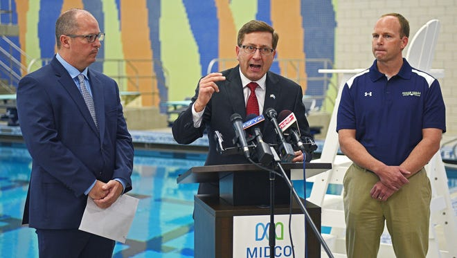 Sioux Falls Mayor Mike Huether speaks as Don Kearney, left, director of Sioux Falls Parks and Recreation, and Jason Ahrendt, right, president of the Sioux Falls Swim Team, look on during a press conference at the Midco Aquatic Center in Sioux Falls Wednesday, Nov. 30, 2016, announcing the booking of four swim meets at the facility next year.