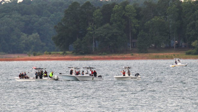 Emergency rescue workers and divers search for a man who fell over a boat in Lake Hartwell Saturday afternoon.