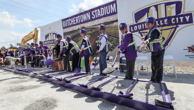 LouCity head coach James O'Connor, right, throws a shovel of gravel during the groundbreaking, along with Mayor Greg Fischer, Governor Matt Bevin and co-owner Mike Mounjoy, for the new Butchertown Stadium where the team will play beginning in 2020.June 28, 2018