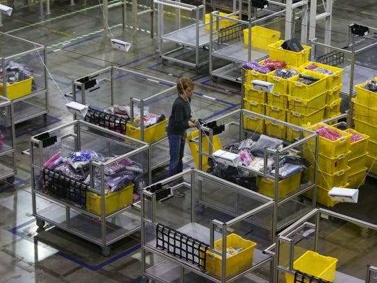 Employees work to fulfill orders at the Amazon Fulfillment