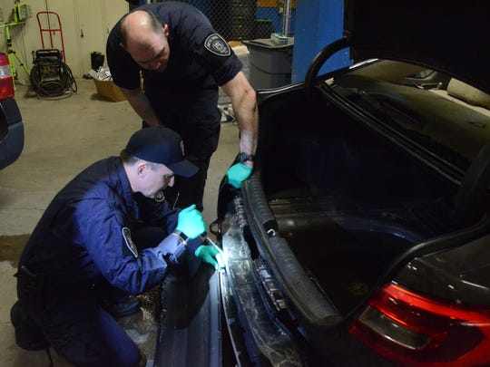 Sgt. Brett Weiss, kneeling, and Corporal Andrew Olsen inspect a hole in the rear bumper.