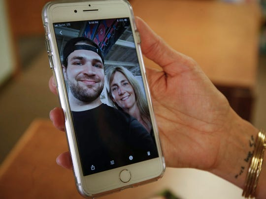 Nikki Dean of Cumming holds a cell phone photo of her and her son, Sam, who died of a heroin overdose on Sept. 26, 2016.